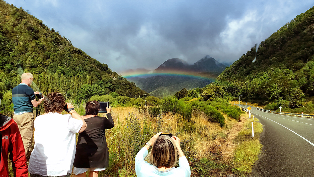 Rainbow on the road in the Southern Alps - Driving in New Zealand for Tourists