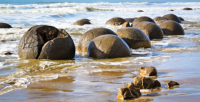 Wierd shaped boulders in the surf, Moeraki Beach New Zealand