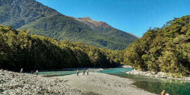 Visitors walking by the river at the Blue Pools in Mt Aspiring National Park - New Zealand Tours