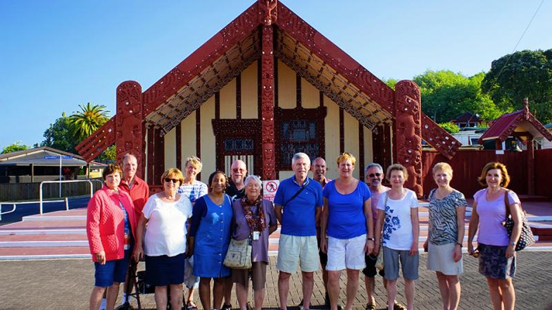 Group photo in front of Ohinemutu Marae meeting house, Rotorua - NZ Sightseeing Tour