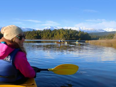 Kayaker on Okarito Lagoon, snowy Southern Alps in the distance