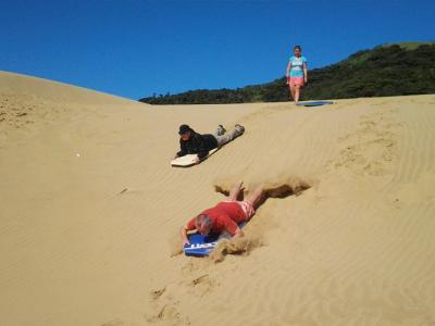 Sliding down sand dunes on a boogy board is awesome fun
