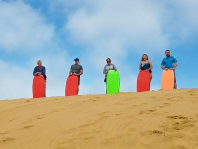 Colourful sandboarders in the Hokianga