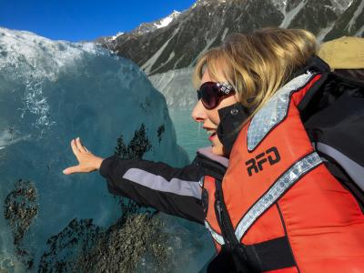 Our guest Carolyn touching an iceberg at the Tasman Glacier