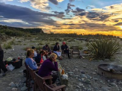 Travellers watching the sunset on the beach in Punakaiki