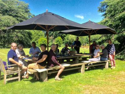 Tour group enjoying outdoor garden lunch in Canterbury