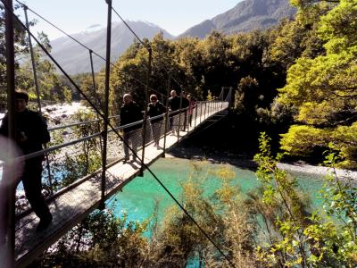 Walking over the Haast River swingbridge, Mt Aspiring National Park with MoaTrek