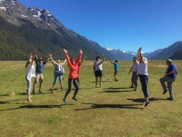 Solo travellers jumping for joy in the Eglinton Valley, Fiordland