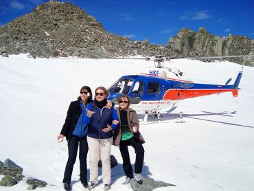 Three travellers posing for a photo in front of their helicopter on Franz Josef Glacier - NZ Glacier Tours