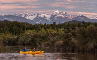 Franz Josef Glacier at sunset, photo from Okarito lagoon with kayaker in foreground - NZ Glacier Tours